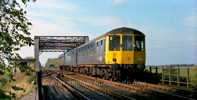 A Birmingham RCW dmu crosses the 100ft drain near Pymore on a Peterborough to Norwich working.  21st October 1977