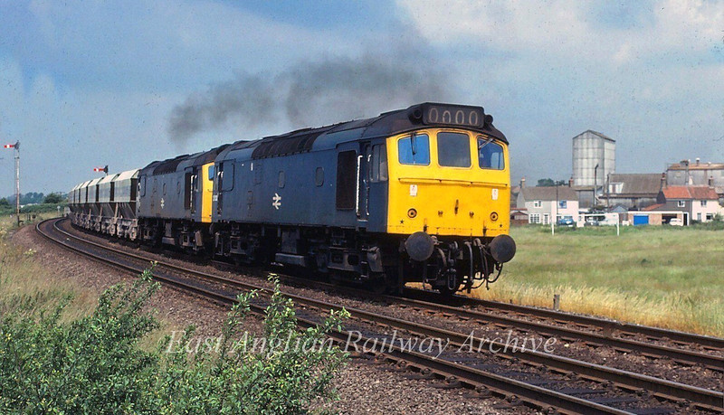 The 0948 Mountsorrel to Kennet passes Eastbound through Soham with 25120 and 25145 forming the motive power. Soham Mill is in the background. 25th June 1980