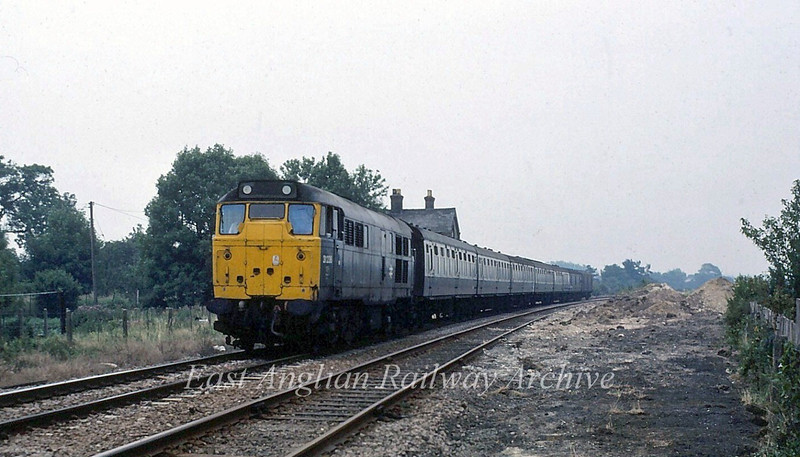 31236 passes the remains of Fordham Station with the 1240 Parkeston Quay to Peterborough. Single line working is in force.  26th July 1980