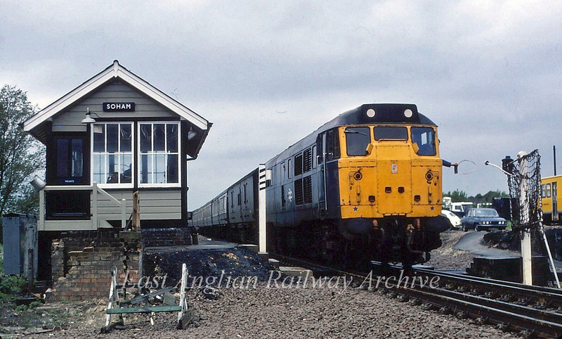 An unknown 31 on a  Peterborough to Parkeston Quay working drops the key token for the single line section from Ely Dock Junction at Soham during May 1981. At this point the track becomes double through to Chippenham Junction. Soham Signal Box is no longer in existence at this site. The original station and box were destroyed by an ammunition train exploding during the Second World War.