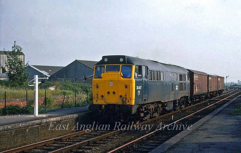 31417 dropping off the single line token at Soham for the temporarily singled Soham to Chippenham Junction section.  27th August 1980