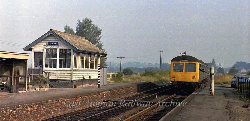 The driver of the 0704 Leicester to Harwich Parkeston Quay drops the single line token for the Ely Dock to Soham section.  30th August 1979.