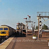 The scene at Ely on the 17th August 1978 with a nice array of semaphores. The 0728 Harwich Parkeston Quay to Manchester Piccadilly is arriving behind 47017. On the right can be seen redundant coaching stock including some pullman cars, destined for Kings Scrapyard at Snailwell.