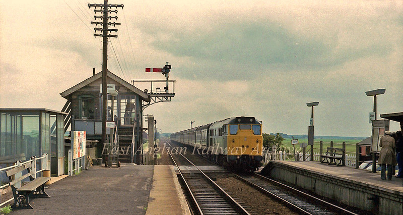 Passengers step away from the platform edge as 31220 passes Shippea Hill with the summer Saturdays only Yarmouth to  Manchester on 22nd July 1978.