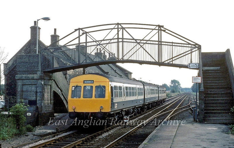 A class 101 is framed by the old footbridge at Brandon. The working is the 1013 Ely to Norwich on 5th September 1980.