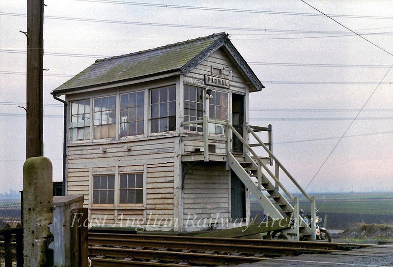 Padnal Signal Box between Ely North Junction and Shippea Hill. The box was destroyed by fire when the stove was left alight. The backdrop is of a typical fenland landscape where the surrounding flat fields are below the level of railways and roads. Photo dated  29th January 1980.