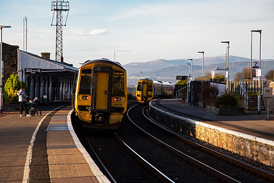Pockets of snow lie on the mountains above Dingwall in the distance.  The up side buildings are all boarded up and disused whilst the down side buildings have long gone replaced by bus type shelters.  The down train is approaching leaning into the curve.