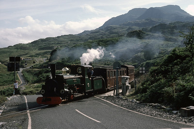 Linda crossing road below Tanygrisiau.  Linda was, at this tiem, running with a gas-producer system.   I think this is why there is steam coming from the cab roof .   The stovepipe chimney did nothing for her appearance 27/07/87