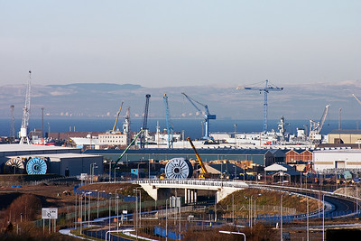 Part of the Naval Dockyard at Rosyth with a couple of warships moored up. Across the River Forth is part of Grangemouth oil refinery.