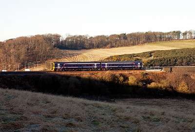 A class 158 sprinter comes off the viaduct working 2G47 0834 Newcraighall to Edinburgh via the Fife Circle outer or clockwise. The grass in the field where the sun hasn't and won't reach is still white with frost!