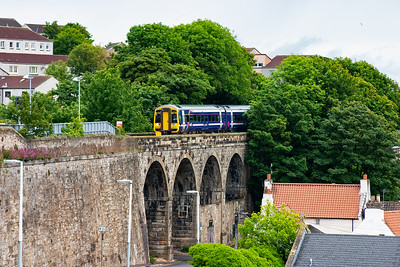 Kinghorn on the Fife coast with the Firth of Forth and ScotRail sprinter 158717 passes over the viaduct and through the station non stop with an unknown working.
