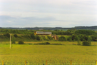 On the Newburgh branch, a class 158 sprinter crosses over the A91 with an evening train to Inverness. 1H19 is booked off Edinburgh at 1940 for the Highland Capital.  7/7/1998