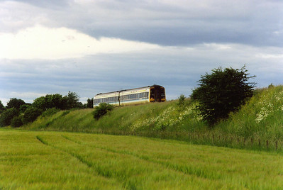 The running gear of 158733 is lost in the long grass of the embankment behind Kettlebridge. The unit is heading for Edinburgh with 1B36 1910 off Perth via the Newburgh branch. It would have left after an Inverness to Glasgow Queen Street had come into the station to connect with it.