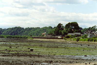 An empty rake of MGR hoppers climbs away from the shoreline of Oakum Bay and will head inland for Dunfermline. 56033 powers 6D72 1430 Longannet Power Station to Mossend Yard.