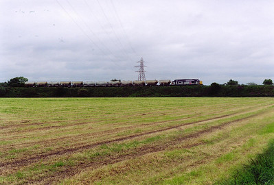 The train gains the southbound road of the main line at Thornton South Junction. The rake is 12 tanks and hoppers probably loaded with flyash from Longannet power station for making into cement.  11/6/1999