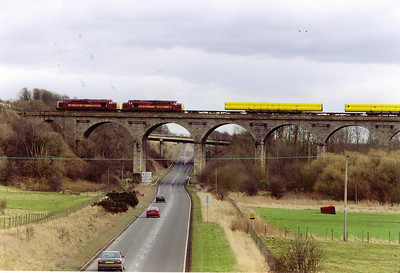 A brace of type 3 locos pass over Markinch Viaduct with the loaded pipes for Inverness, 6X88. 37718 and 37883 front the train, 0610 from Hartlepool to Inverness, Mondays and Wednesdays only. The overhang of the pipes is most obvious in this shot.  17/2/2000