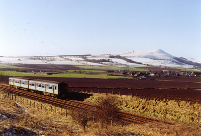 On the high ground of the Lomond Hills, the Paps o' Fife, a mantle of snow lies crisp and frozen. 150283 descends Falkland Road Bank at Welltree with 1L57 1115 SuO Edinburgh to Dundee.