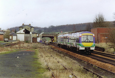 A down train from Edinburgh to Aberdeen, 1310 off, 1A65, slows for its station stop. The Grade 2 listed former goods shed is slowly falling apart since the A4 pacific 60009 Union of South Africa moved out in 1993.