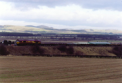 The light has gone unfortunately when 66021 appears with the empty pipe carriers from Inverness to Hartlepool, 0820 off 6E69 ThSO.  22/1/2000