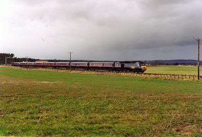A short while later a down HST operated by GNER comes by beneath a stormy sky. Heavy rain is not far away as the 0710 Leeds to Aberdeen, 1S11, nears the level crossing.  28/2/2000