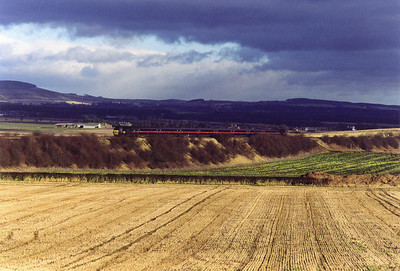 Dark and threatening skies gather as an unknown GNER high speed train heads south with 1E12 0955 Aberdeen to Kings Cross on the climb of Falkland Road Bank.  22/1/2000