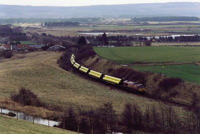 Collessie Den is the location for 66164 working the loaded pipe train, 6X88 MWO 0610 Hartlepool to Inverness. The train is worked on to Georgemas Junction later in the day. 21 bright yellow pipes form the payload.  3/2/2000