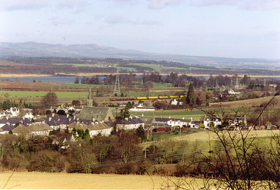 Happy birthday to me! A sunny day and 66123 is back with the loaded pipe train as it heads north past the village of Abernethy with the River Tay in the background.  21/2/2000