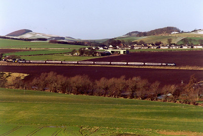The sun shines down from a cloudless blue sky with the village of Dairsie in the background. A GNER working from Aberdeen to Kings Cross passes by. This is 1E08 0950 SuO working.  13/2/2000