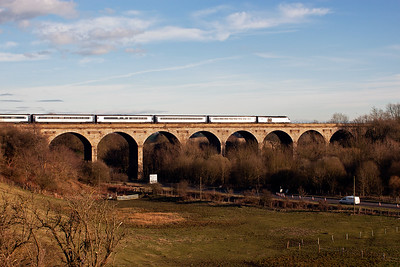The mid afternoon Aberdeen to London Kings Cross East Coast service glints as it flashes over the viaduct the lead powercar shines in the sun. This train is 1E24, 1450 from Aberdeen.