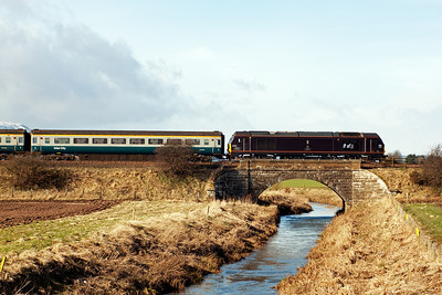 The EWS type 5 loco in Royal Claret livery crosses the small bridge taking the line over the River Eden.