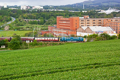 The train slows for its Markinch pickup, the former Haig's Whisky building forms the impressive backdrop and in the distance is one of two large viaducts on the former Leslie branch, now a footpath.
