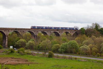 The North British Railway built structure is slowly being swallowed up by the bushes and the trees on both sides. A class 170 turbostar in the new ScotRail livery accelerates away from the station working 1L62 1130 from Dundee to Edinburgh.