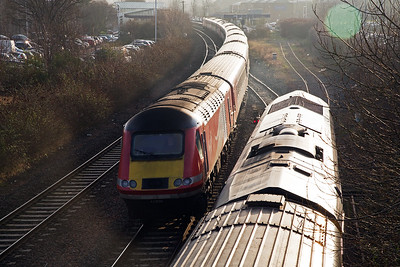 The carpark to the left is where the goods shed once stood and the car park to the right was once the down freight yard.  43296 passes 66740 as the rear powercar 43317 is still passing through the station.  This VTEC working is 1S11 1000 off Kings Cross to Aberdeen.