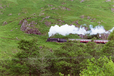 The approach to Glenfinnan station is severe on a 1 in 50 climb. Despite the loco working hard, the fireman will be starting to cool his fire down for the 20 minute wait at the station.