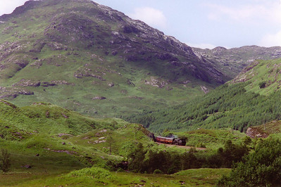75014 and its train drifts through a cut in the rock as it comes towards Glenfinnan. Sgurr a Mhuidhe fills the picture to a height of 1,826 feet.