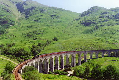 A classic shot and a classic location, 44767 comes round the famous Glenfinnan Viaduct. Like all the bridges and viaducts on this line it is built of reinforced concrete.