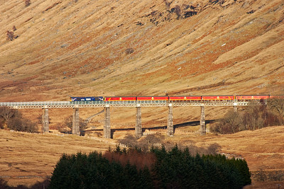 The sun is almost glinting off the first vehicle of 325002 as it passes over the viaduct over the Auch Glean stream.