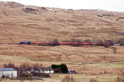 The line clings to the hillside as it slowly gains height rising at a ruling gradient of 1 in 60. Here 66728 with 325008 and 325002 pass near Auchtertyre with Tyndrum Upper a few miles away.