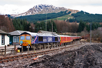 "66728 rolls into Crianlarich station on the falling 1 in 264 gradient. The loco is carrying John Hynd's ""The West Highlander"" headboard so it would be a safe bet to say he was the route conductor for this working."