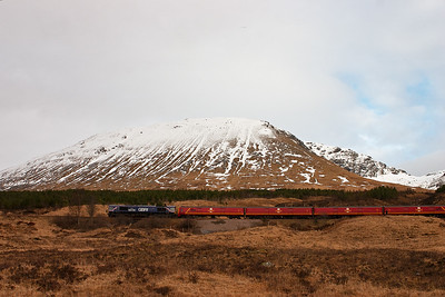 As 66728 and the mail EMUs gather speed away from Bridge of Orchy, with snow capped Beinn an Dothaidh forming the backdrop.