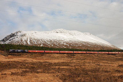 The snow capped hill in the back ground is the northern flank of Beinn Dorain and the most unusual train passes below it.