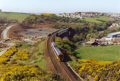 The view from the top of the rock cutting just south of Jamestown Viaduct is superb as 158734 heads south with 1B35 1408 from Aberdeen to Edinburgh. The gorse bushes in bloom give the fields a warm yellow colour.