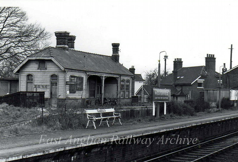 Westerfield, junction for the Felixstowe branch on 1st April 1977 with blue Eastern Region nameboard. The building behind the bay platform is the original terminus for The Felixstowe Railway and Pier Company Railway, now converted to a private residence.  The large building in the middle is The Railway Public House.