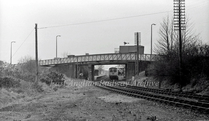 Oulton Broad South Station viewed from  near the location of the Oulton Broad South Signal Box. The track bed of the  line to Kirkley and Lowestoft South Side is to the left with the sharp curve towards the swing bridge to the right. The Cravens unit at the platform is the 1155 Ipswich to Lowestoft. 25th March 1977.