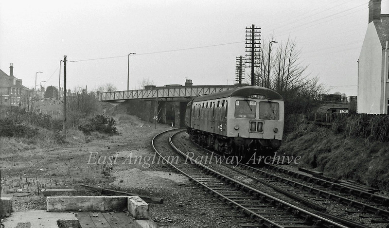 The 1155 from Ipswich rounds the curve away from Oulton Broad South on 25th March 1977. The trackbed of the former goods line to Kirkley and Lowestoft South Side is on the left. The remains of the Oulton Broad South Junction signal box can be seen in the foreground.