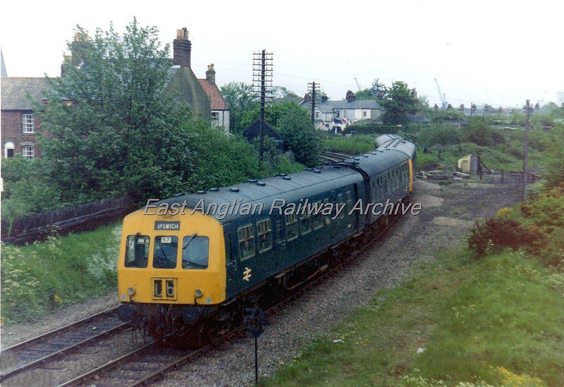 Class 101 heads the 1554 Lowestoft to Ipswich at what was Oulton Broad South Junction. The track bed to the right went to Kirkley and Lowestoft South Side.To the right of the dmu can be seen the remains of the junction signal box. Image dated  Sunday May 17th 1975. The line to Lowestoft South Side closed in 1970. See next photo.