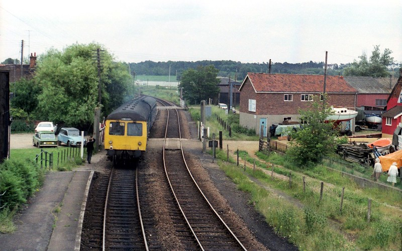 View from the Woodbridge footbridge facing north on 29th June 1979. The 1448 Ipswich to Lowestoft is passing Ferry Lane Crossing. To the right of the concrete crossing gate post was the route of the Woodbridge to Melton tramway.