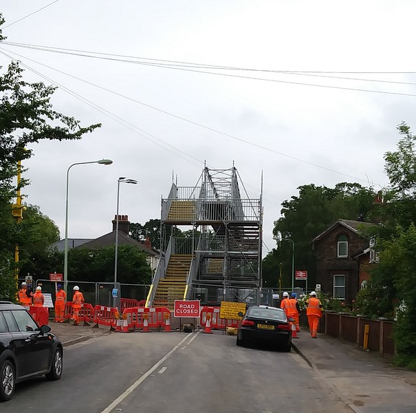 During the summer of 2019, the B1077 road which crosses the East Suffolk line at Westerfield was closed while Network Rail carried out conversion work on the crossing from AHB to full barriers. This was the scene  on 12th June 2019 showing the temporary footbridge  over the line.