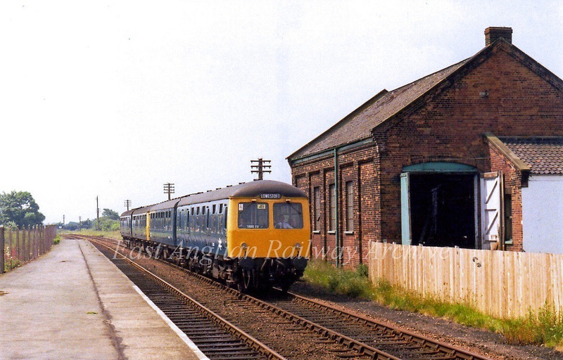 The 1048 Ipswich to Lowestoft formed of 2 X 2 car Cravens Units approaches Wickham Market on 28th June 1979. The goods shed on the right was recently demolished for housing. A local campaign to save it was unsuccessful.