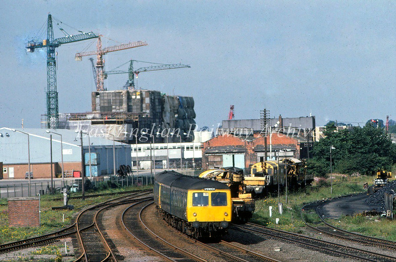 Dwarfed by tower cranes on rig construction work, the 0904 from Ipswich approaches it's destination at Lowestoft.  30th August 1980. Photo taken from the footbridge linking Denmark Road and Commercial Road (Iron Bridge). Coke Ovens Junction where the line to Yarmouth diverged is to the right behind the trees. Pictures of the footbridge in the next two photos.